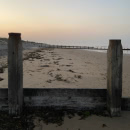 Wooden posts on the beach, framing the sunset.